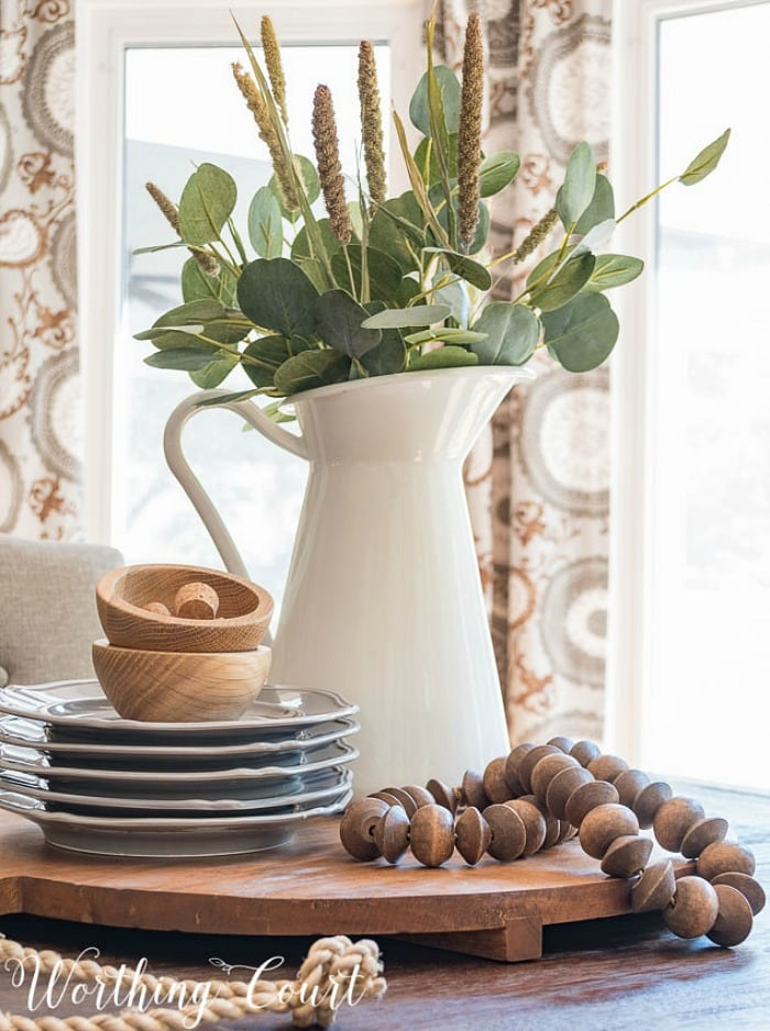 centerpiece on a round board with gray and wood accessories and eucalyptus stems in a white pitcher