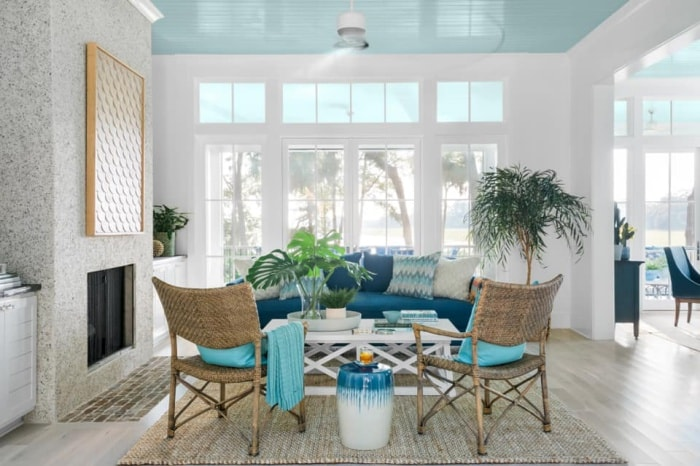 sunroom with blue ceiling, white walls, rattan chairs, blue couch and accessories