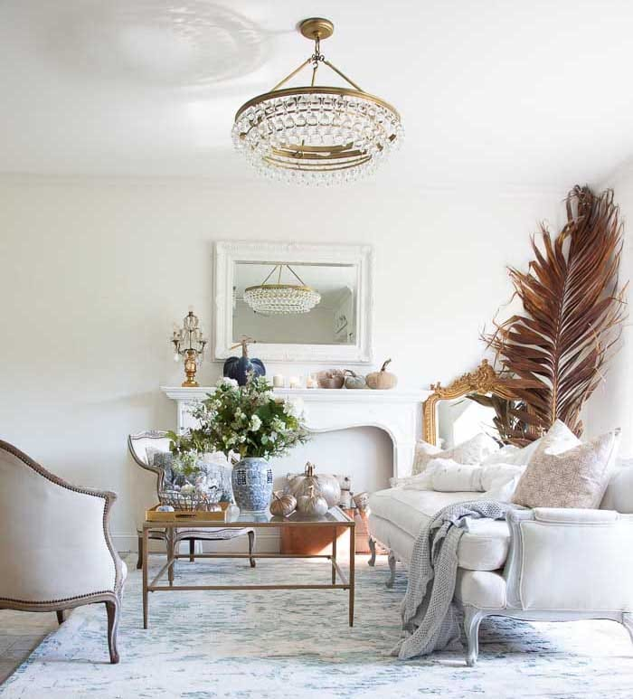 living room with white walls and furniture, a crystal chandelier, a square coffee table and accessories