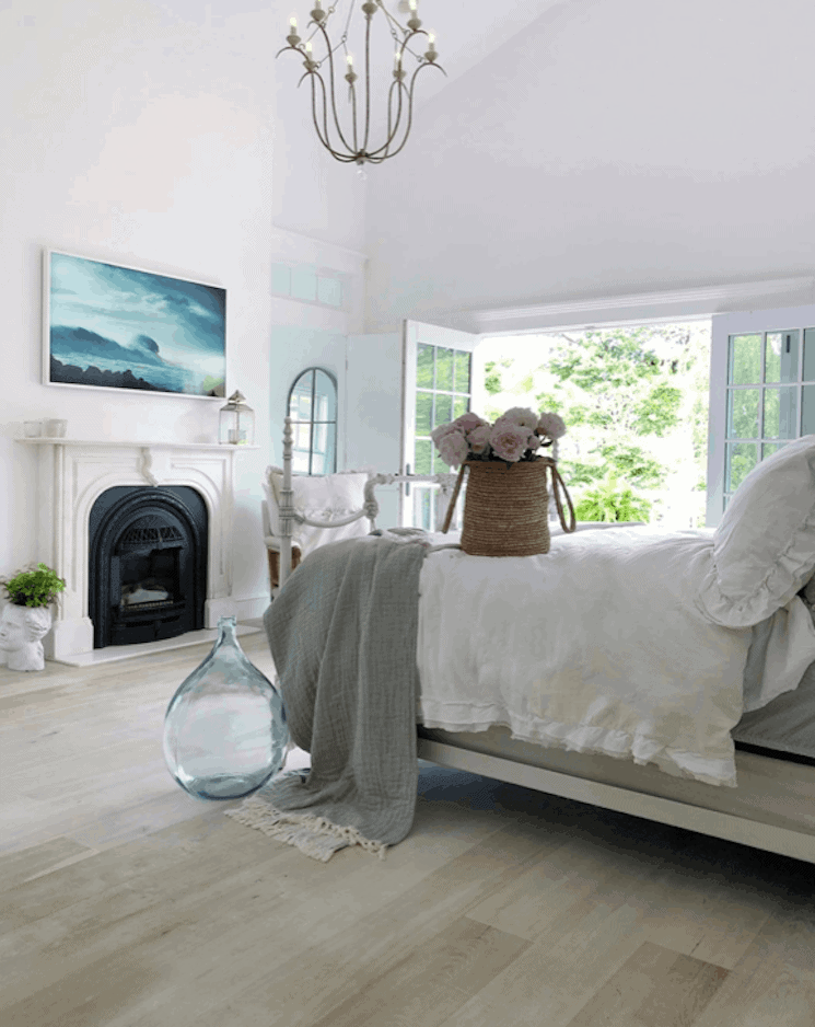 bedroom with white walls, a fireplace, white bedding and gray floors