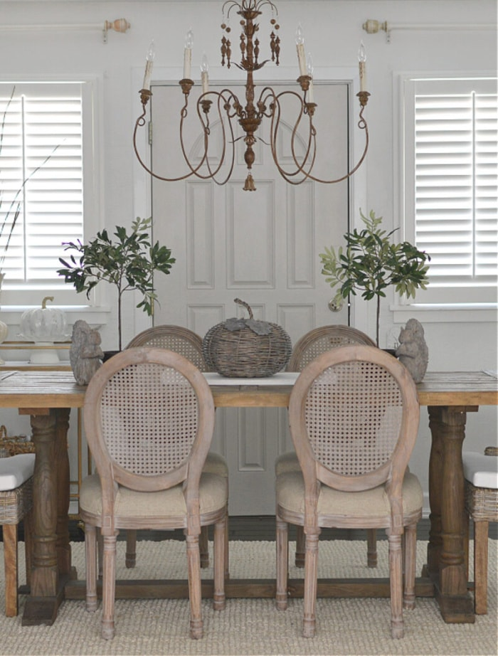neutral dining room table and chairs with chandelier above with a fall centerpiece