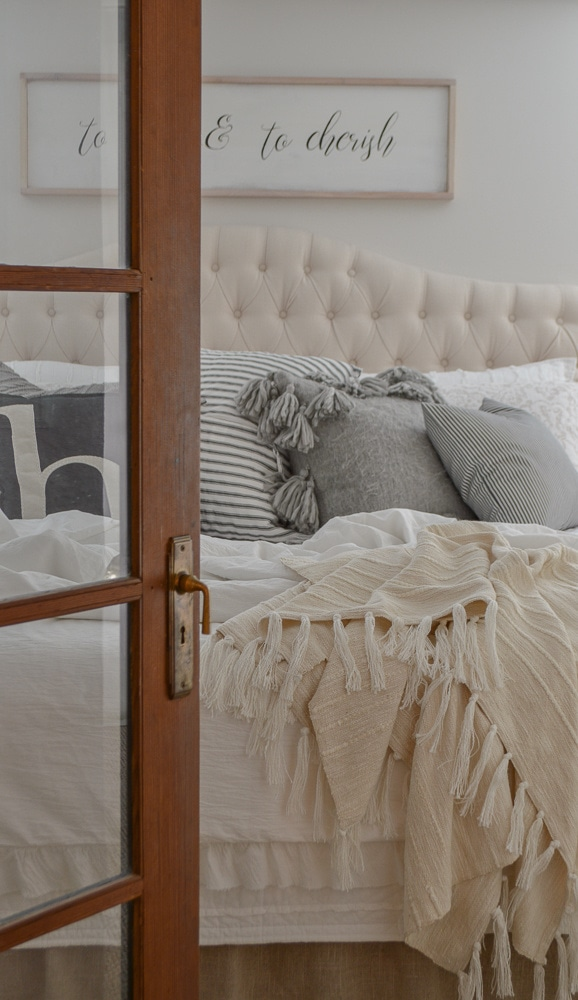 view looking through a french door into a bedroom with a white bed with white bedding