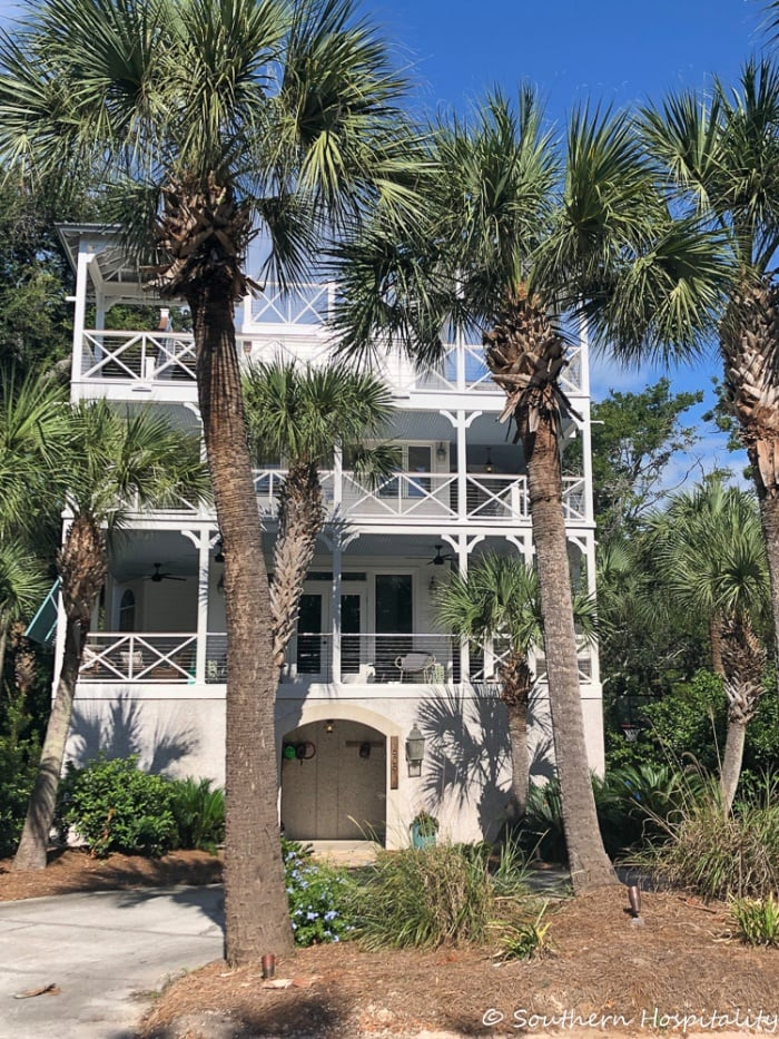 3 story coastal house with palm trees in front