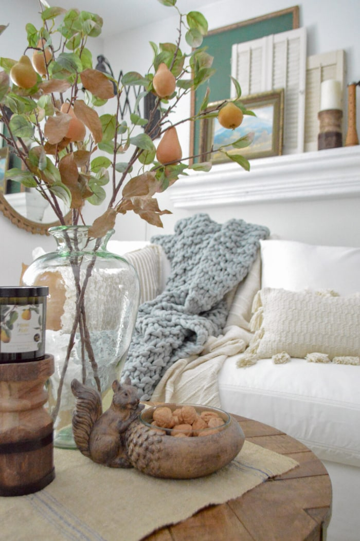 glass vase containing faux pear stems in front of a white couch