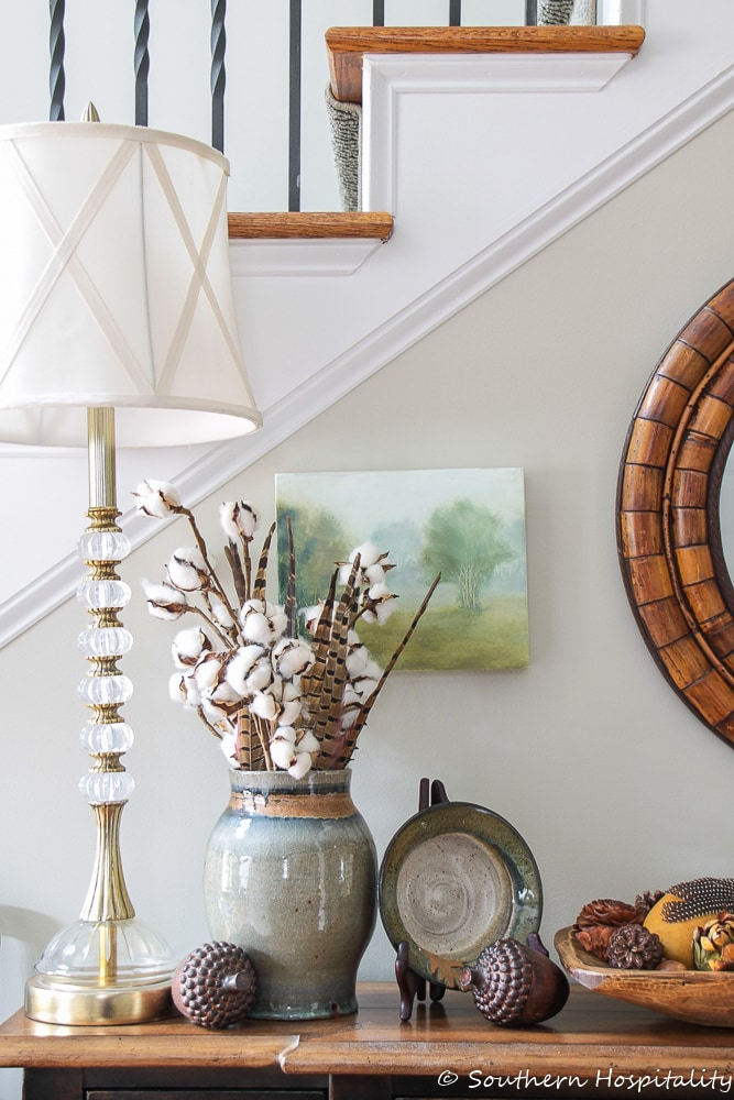 fall vignette on a console table with cotton stems, feathers and a glass lamp