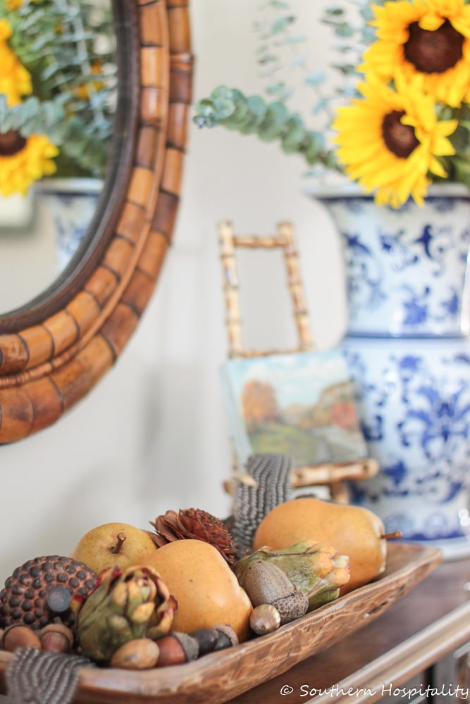 fall tidbits in a wooden dough bowl on a console table