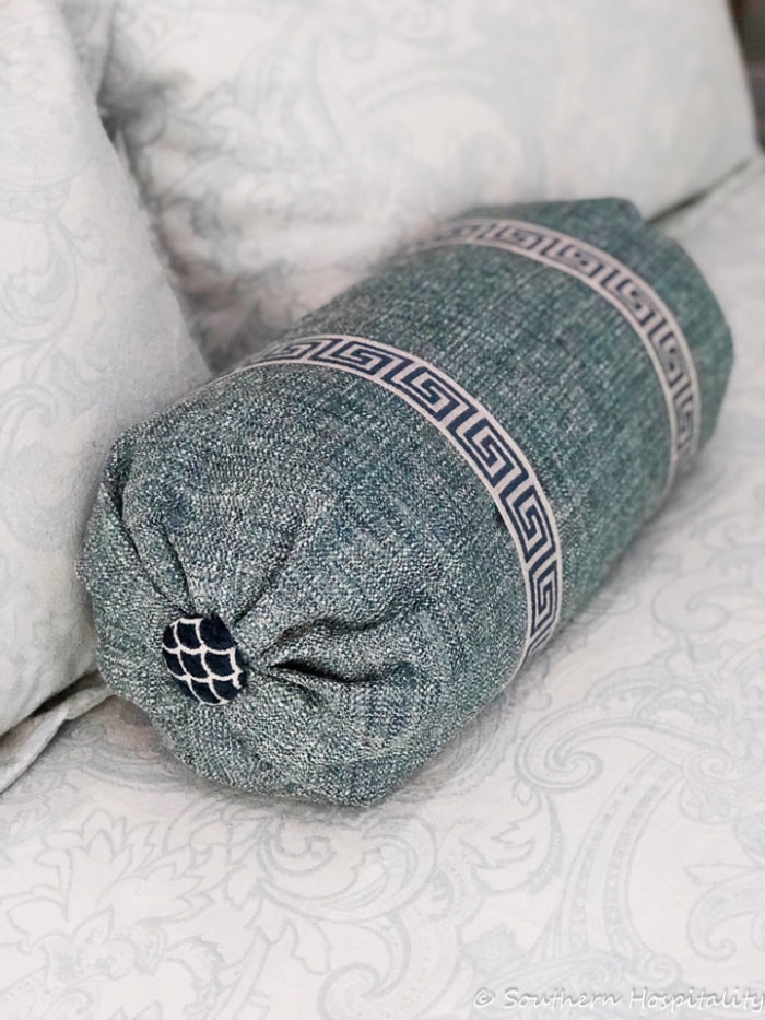 blue bolster pillow with greek key trim and a covered button on each end