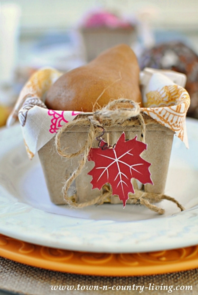 berry basket filled with a napkin and dried gourd with a paper leaf on the end