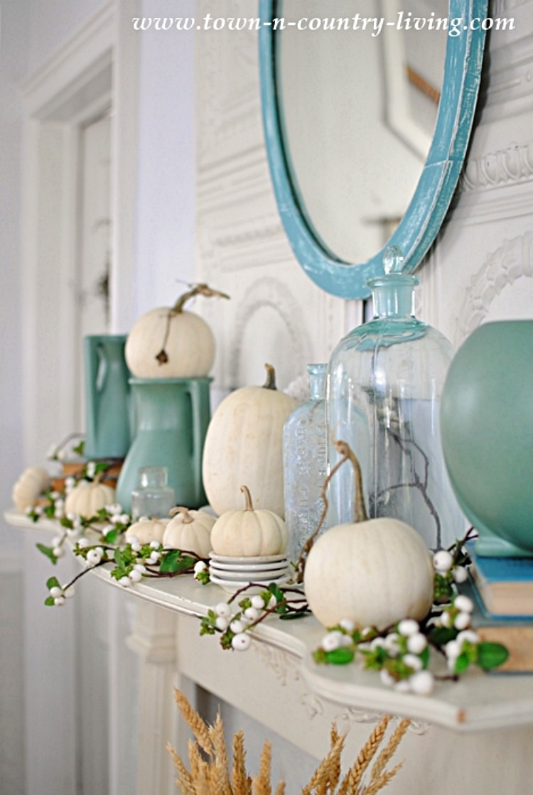 mantel with white pumpkins, blue vases and glass bottle with a blue framed mirror hanging above