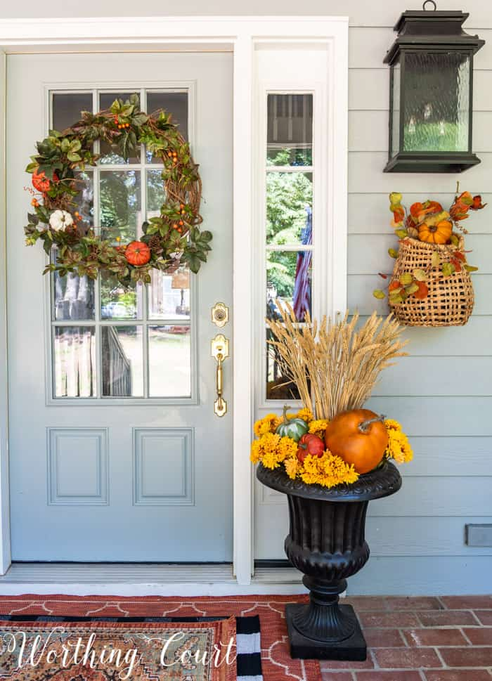 fall urn beside gray front door with fall wreath