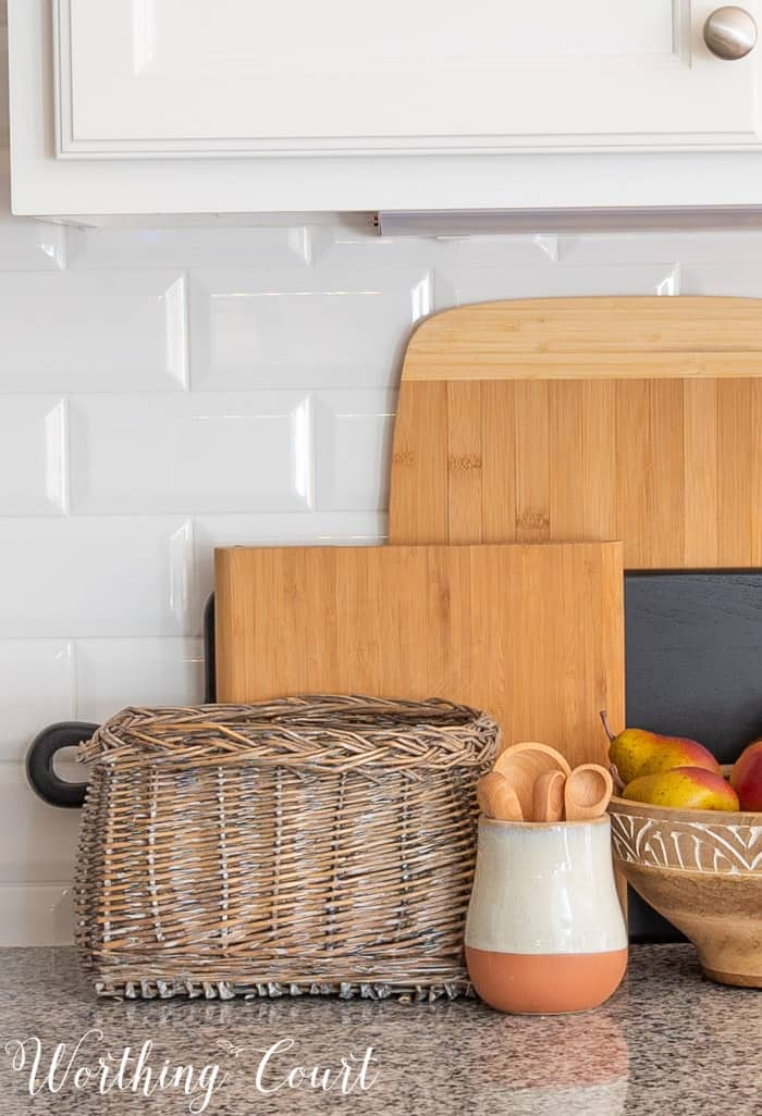 stacked wood cutting boards against a white subway tile backsplash with a basket, wooden bowl and small crock in front
