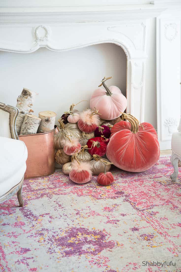 stack of tumbling velvet pumpkins in shades of pin in a faux fireplace