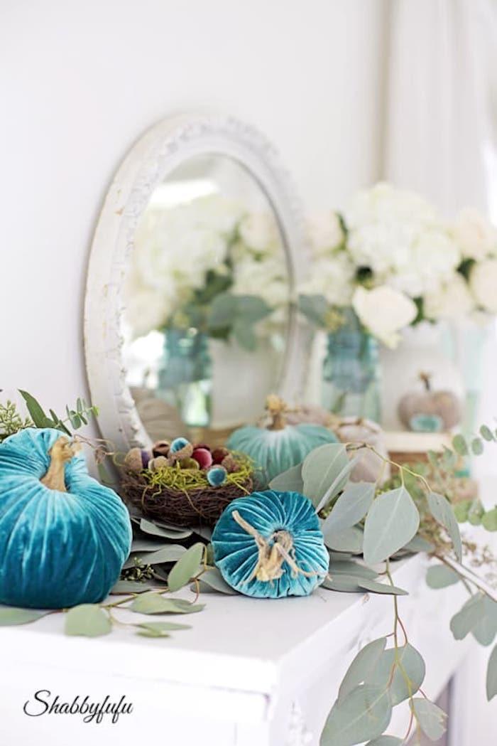 blue velvet pumpkins and eucalyptus on a mantel