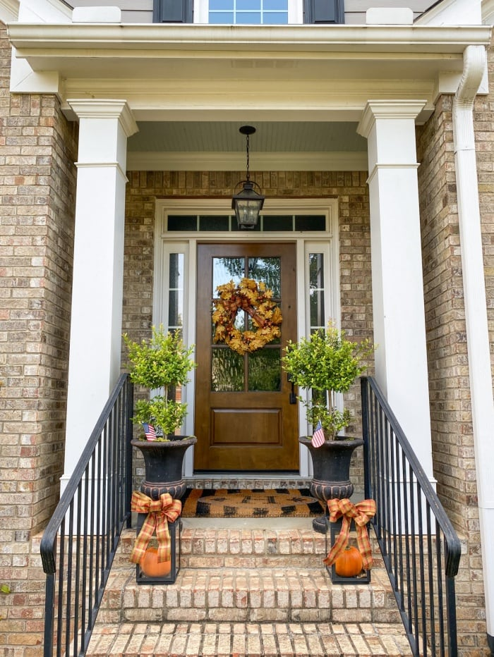 front porch with brick steps and wood door with matching topiaries and fall lanterns