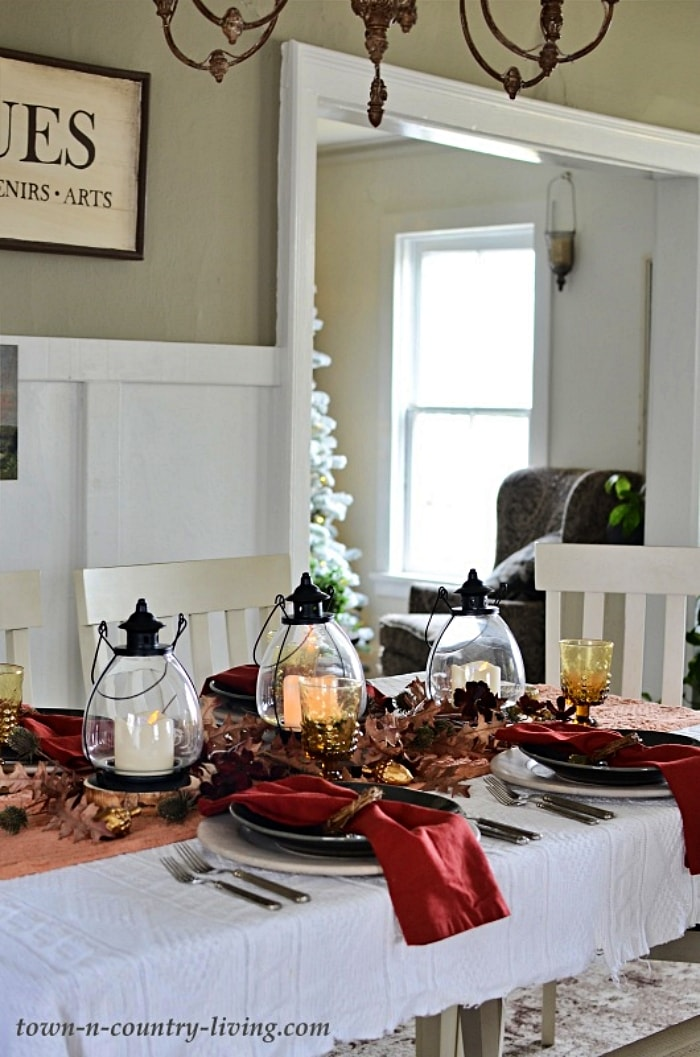 table setting with white tablecloth, rust colored napkins and three black lanterns with candles